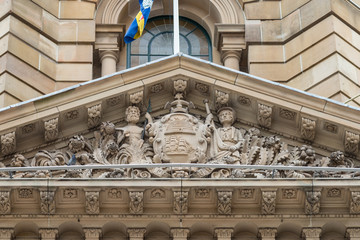 Sydney, Australia - March 25, 2017: Closeup of top of brown stone Town Hall focus on frieze with statues in front facade above entrance.