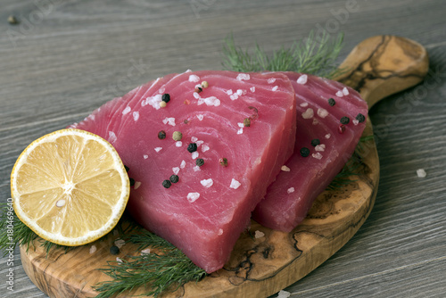 Fotobehang Steakhouse Raw tuna fillet with dill, lemon and peppers in olive cutting board