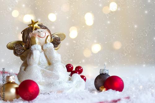 Weihnachtsengel sitzend mit Weihnachtskugeln