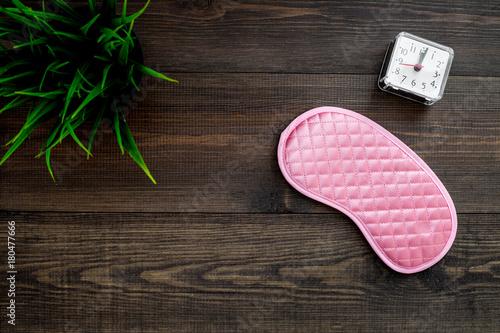 Healthy sleep concept. Sleep mask, plant, alarm clock on dark wooden background top view copyspace - 180477666