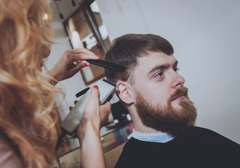 Master cuts hair and beard of men, hairdresser makes hairstyle for a young man. Hipsters