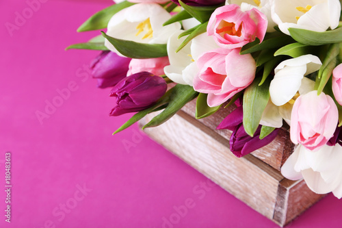 Bouquet of tulips in crate on pink background - 180483613