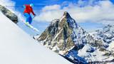Man jumping from the rock, skiing on fresh powder snow with Matterhorn in background, Zermatt in Swiss Alps. - 180483860