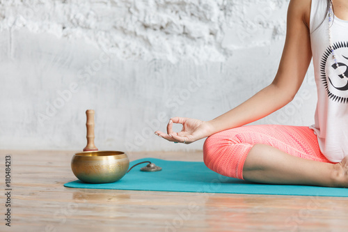 Wall mural Young woman meditating in a yoga on white background, Yoga and healthy lifestyle concept