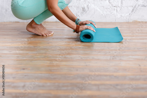 Poster Close-up of attractive young woman folding blue yoga or fitness mat after working out at home in living room. Healthy life, keep fit concepts. Horizontal shot. white loft studio