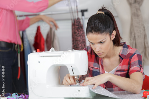Plakat young woman is sewing cloth with sewing machine