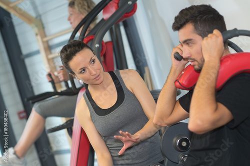 Poster man and woman talking in gym