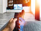 Zappen / Fernsehen auf der Couch mit Fernbedienung in der Hand - 180490017