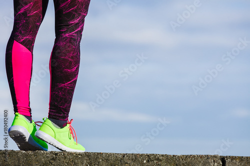 Poster Female legs feet in vivid color yellow shoes on seaside.