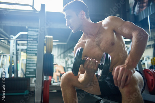 Poster Portrait of handsome muscular man with bare chest working out with dumbbells sitting on bench in modern gym, copy space
