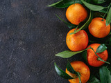Tangerines, oranges, mandarins, clementines, citrus fruits with leaves on black cement background. Top view or flat-lay. Copy space.