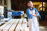 Portrait of mature bearded carpenter posing confidently with arms crossed standing in and smiling happily looking at camera - 180494862