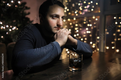 man with glass of whisky in the pub on night  © alexkich
