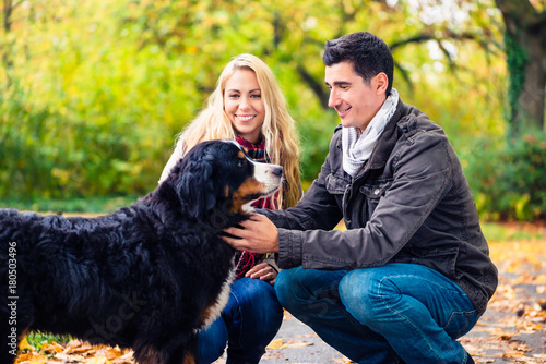 Couple with dog enjoying autumn or fall in nature Poster