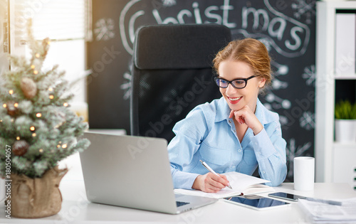 Wall mural businesswoman freelancer working at a computer at Christmas