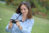 Lady looking digital camera screen - 180504667