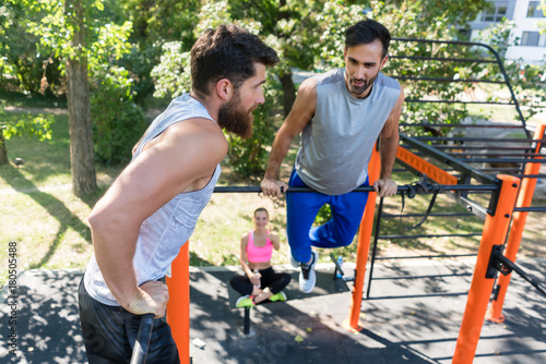 Fototapeta Two muscular young men doing bodyweight exercises for the upper-body motivated by their female friend in a modern fitness park in summer