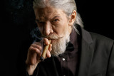 Stylish old man smoking cigar. Aged male in black suit in studio. - 180507680