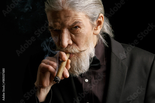 Stylish old man smoking cigar. Aged male in black suit in studio.