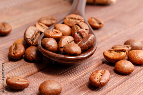 Papiers peints Café en grains Grains of coffee close-up. Coffee beans are located on a spoon among the wooden texture. Coffee grains are located on a spoon on a wooden. Java composition from whole grains of coffee.