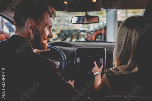 Man and woman sitting on front seats of new car. Happy couple in auto showroom choosing new vehicle.