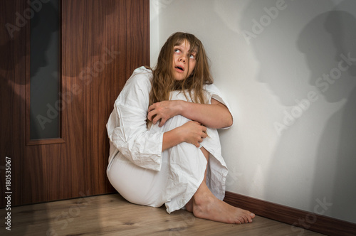 Woman with schizophrenia at room with people shadows