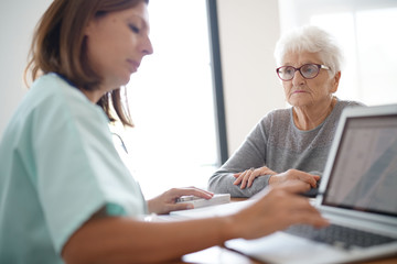 Nurse giving prescription to elderly woman