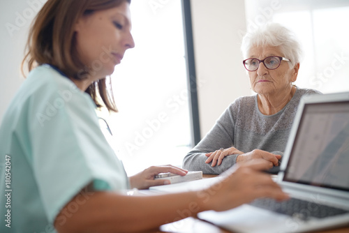 Nurse giving prescription to elderly woman