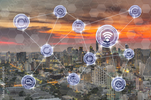 Wireless communication connecting of smart city Internet of Things Technology over the modern cityscape at evening background, technology business IOT concept - 180545428