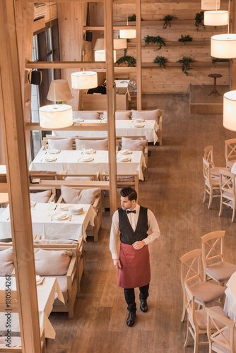 Waiter going between empty tables