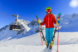 Portrait of happy young girl on the snow with ski in winter time, ski slope and cable car in background. - 180557432