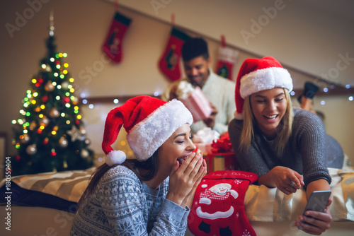 Two gorgeous attractive girls with Santa hats laughing at mobile text while their friend checking Christmas gifts behind them for holidays Poster