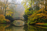 Scenic view of misty autumn landscape with beautiful old bridge in the garden with red maple foliage.