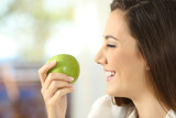 Profile of a woman holding an apple