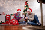 Positive young beautiful parents spending a great time with their happy kid while sitting on a carpet and looking at a tablet in the warm house for Christmas holidays.