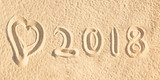 Close up on 2018 written in the sand of a beach wih a heart - 180561855
