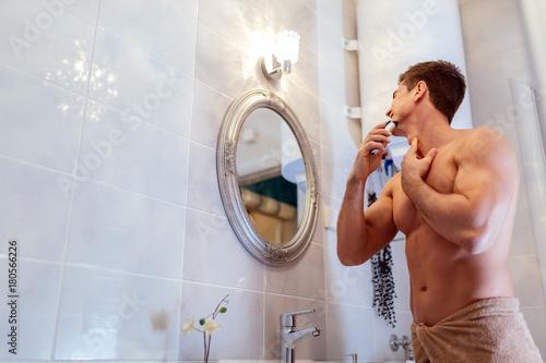 Muscular man shaving in bathroom