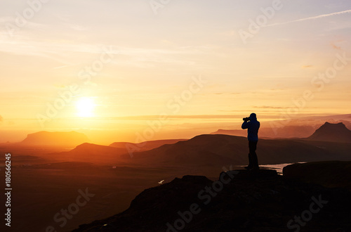 Foto op Plexiglas Chocoladebruin Nature photographer with digital camera on top of the mountain.