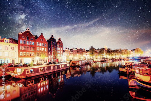Papiers peints Amsterdam Beautiful night in Amsterdam. Night illumination of buildings and boats near the water in the canal