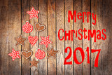 Christmas greeting card 2017, rustic ornaments on wood planks background creating the shape of a Christmas tree - 180567283
