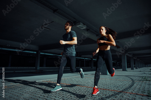Poster Young sports couple running in the urban environment