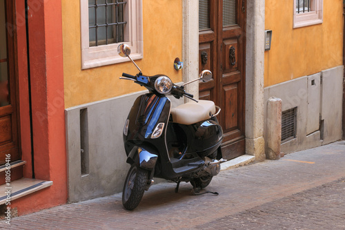 Plexiglas Scooter Urbino, Italy - August 9, 2017: scooter parked on the street.