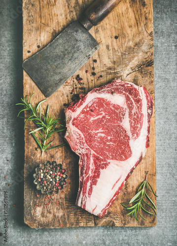 Flat-lay of raw prime beef meat dry-aged steak rib-eye on bone and chopping knife on wooden board over grey concrete background with seasoning, top view. Meat high-protein dinner concept - 180569696