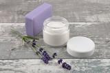 Offene Gesichtscreme und Seife auf verwittertem Holz - 180571057