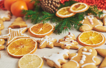 Christmas gingerbread cookies and dried orange and spices on white table. Chairs Christmas trees, cones and Christmas decorations