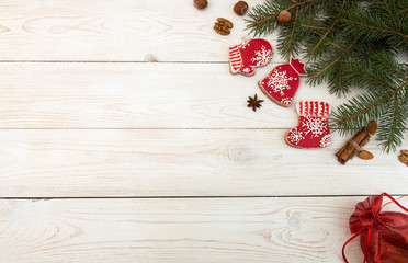 Overhead of Christmas New Year holiday background. Red gingerbread cookies boots, meetens, bag with gift, fir branch tree on white wooden background. Top view.