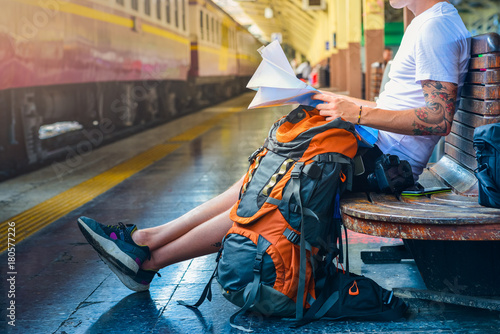 Man holding a map with backpack, camera and a smart phone in a train station