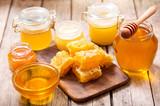 various types of honey in glass jars - 180577403