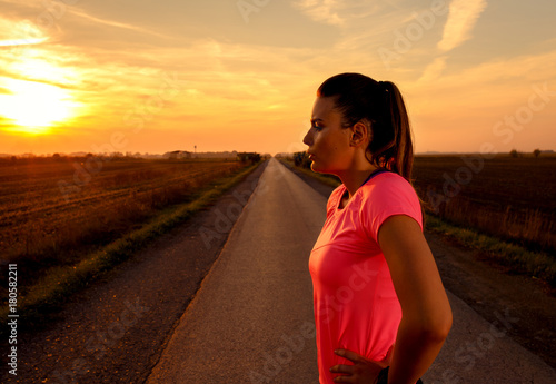 Papiers peints Marron Athletic woman preparing run on rural road during sunset.