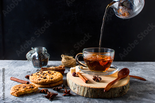 Fototapeta Cup of tea, biscuits, cinnamon, anise on dark background